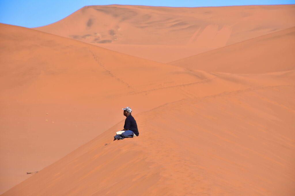 אדם יושב על דיונה נמביה